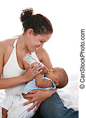 Happy Mother Feeding Baby Boy with Milk Bottle
