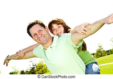Father and daughter piggyback - Portrait of happy father...