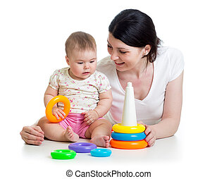 baby girl and mother playing together with toy