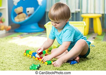 child boy playing with block toys indoor