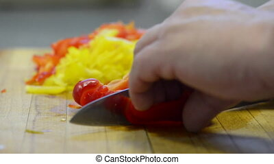 knife cuts vegetables - cook man cuts vegetables on kitchen...