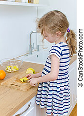 Little girl cutting apple in the kitchen