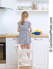 Little girl making meal in the kitchen.