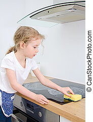 Little girl wipes cooktop in the kitchen at home
