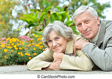 Happy senior couple sitting at table in park