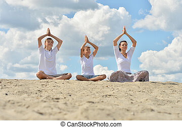 Mother with her sons sitting on a sand and doing yoga
