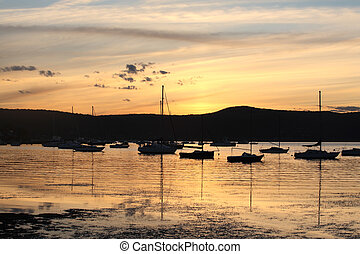 Yachts and boats moored on tranquil waters at sunset - Boats...