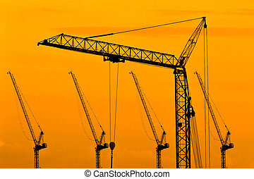 Industrial construction cranes and building silhouettes