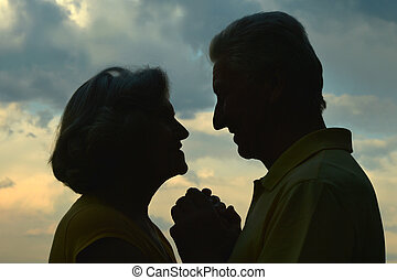 Silhouette of an elderly couple in love at night river