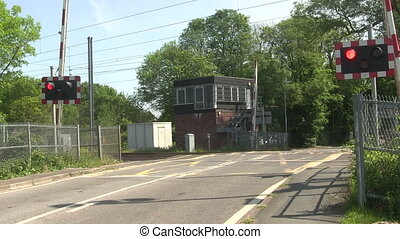 Barrier coming down, level crossing - Red flashing warning...