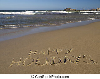 Happy holidays written on the sand beside the ocean.