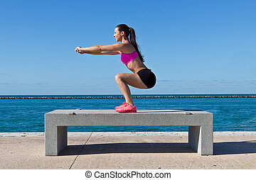 Hispanic woman doing squats by the water - Hispanic woman...
