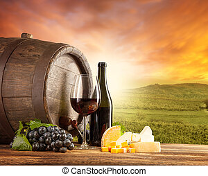 Red wine still life with vineyard on backgorund - Old wooden...