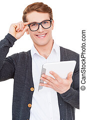 Confident in his gadget. Handsome young man holding digital tablet and smiling while standing isolated on white