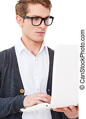 IT guy. Handsome young man working on laptop while standing...