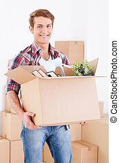 Moving to a new house. Handsome young man holding a cardboard box and smiling at camera while other carton boxes laying on background
