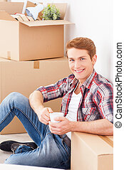 Just moved to the new apartment. Top view of cheerful young man sitting on the floor of his new apartment and drinking coffee while cardboard boxes laying in the backgroundJust moved to the new apartm