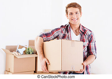 Moving to a new apartment. Cheerful young man holding a cardboard box and smiling while other carton boxes laying on background