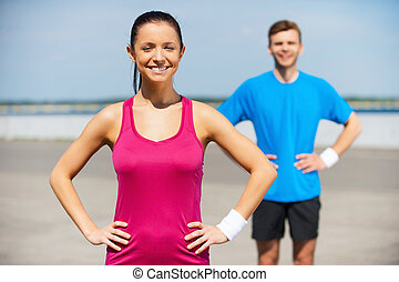 Sporty couple. Handsome young man in sports clothing holding hands on hip while standing outdoors