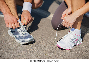 Getting ready to run. Top view of young man and woman tying...