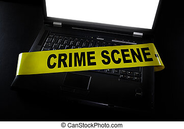 computer crime scene - laptop with crime scene tape across...