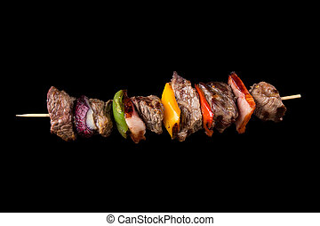 Tasty skewers on black background. - Tasty skewers on black...