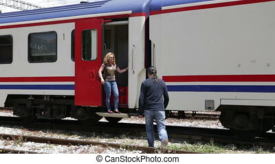 couple holding hands at train stati
