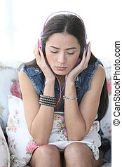 Young woman listening music through headphones, eyes closed...