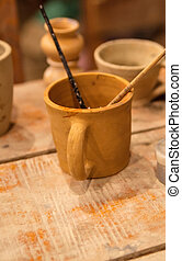 Pottery workshop with clay, pints and tools, editorial photo