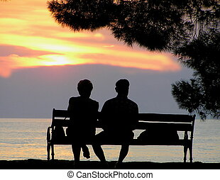 Golden years - Older couple enjoying the ocean view sunset