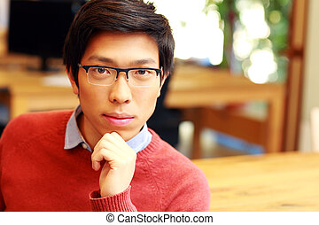Young asian male student sitting in classroom