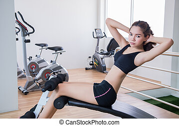young fit woman sit up in fitness room