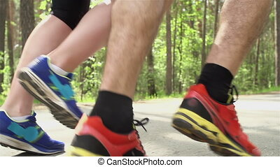 Healthy Lifestyle - Tracking side view of two pairs of feet...