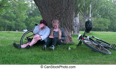 Mother and daughter cyclists resting after cycling in the...