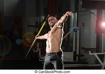 Mature Male Athlete Practicing To Throw A Javelin - Mature...