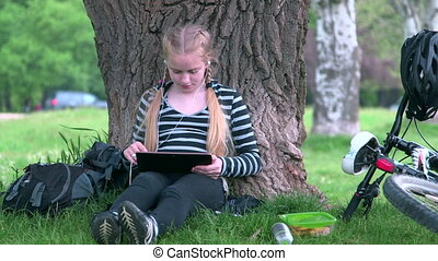 Teenage girl using tablet pc in park - Teenage girl with...