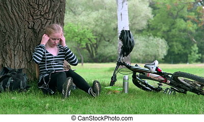 Teenage girl with bicycle resting in summer park