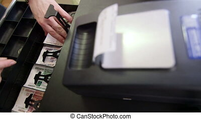 Cashier making change in cash register drawer, russian...