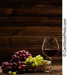 Glass of red wine and grape in basket in wooden interior