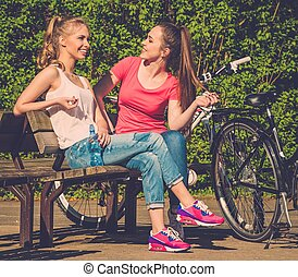 Two happy teenage girls with bicycles in a park