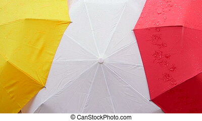 Opened colorful umbrellas in rain background