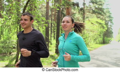 Increasing Physical Fitness - Tracking shot of man and woman...