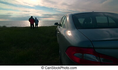 Trip to the sea shore by car - Adult couple near parked car...