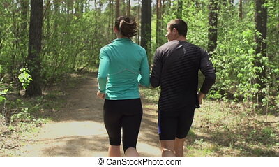 Jogging Together - Tracking shot from behind of boy and girl...