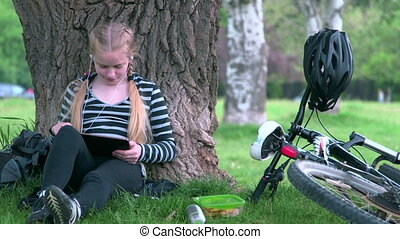 Teenage girl using tablet computer for social networking and...