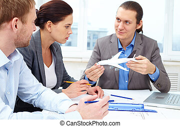 Invention of new plane - Three engineers discussing a small...