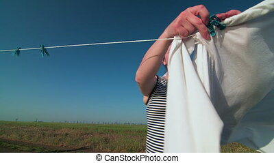 Housewife hanging white laundry on washing line in the field