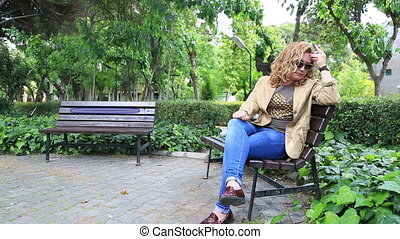 Sad woman smoking in park