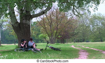 Cyclists resting after riding bicycle in a park