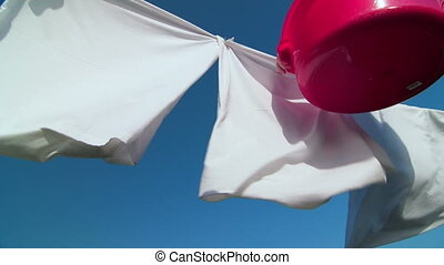 Housewife hanging white laundry on washing line